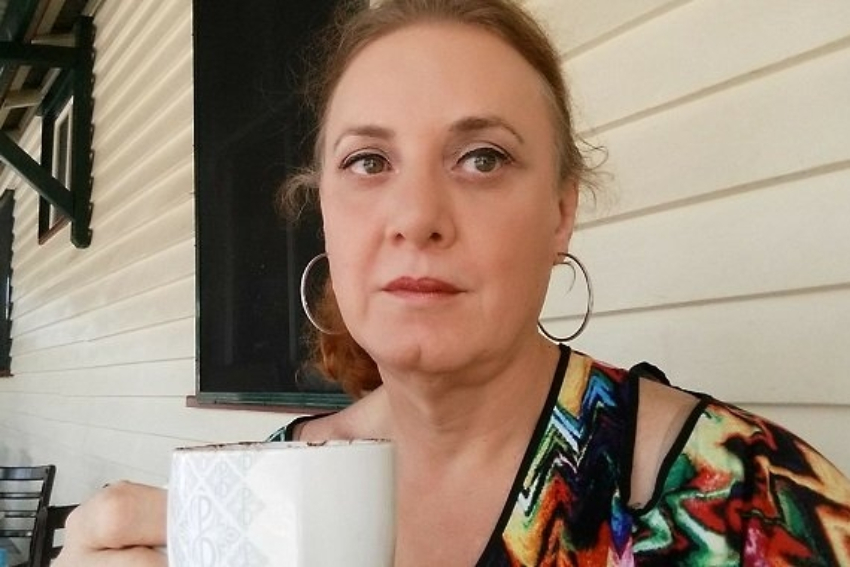 a woman taking a selfie she is holding a white mug and not smiling