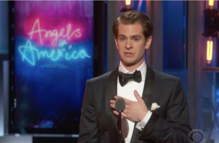 andrew garfield stands on a stage behind a microphone in a tuxedo with his hand on his chest a neon sign saying angels in america is behind him