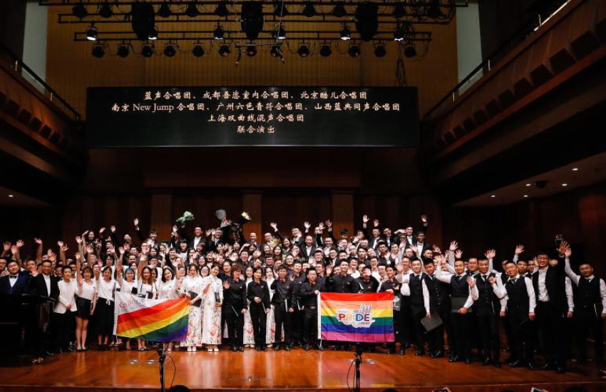 a group of people in formal matching attire are standing on a stage, smiling and waving. some are holding rainbow flags that say 'pride' on them