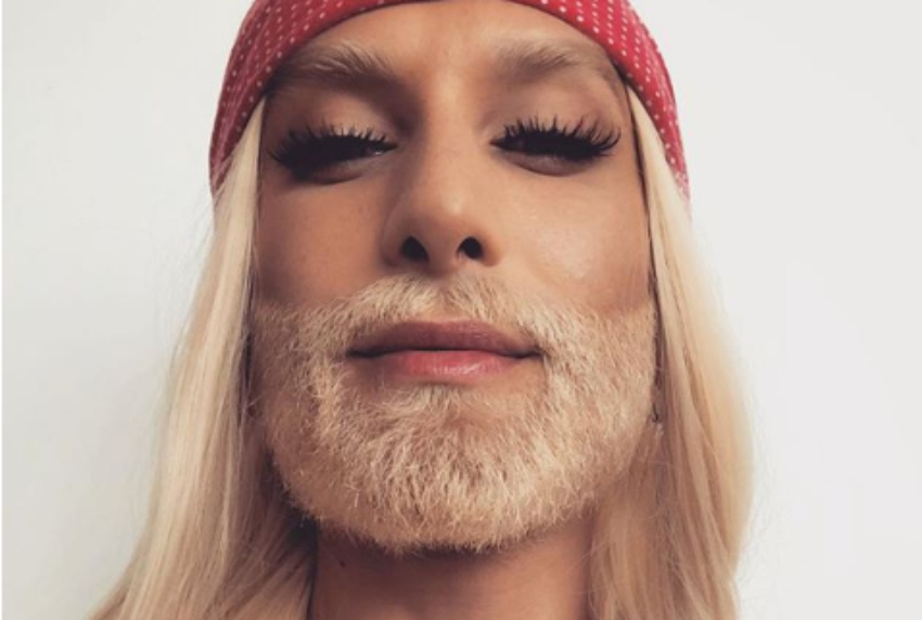 close up of conchita wurst who has a platinum blonde beard and long hair she is wearing a red beanie and false eyelashes