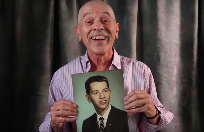 One of the contributors to the video holds a photo of himself when younger
