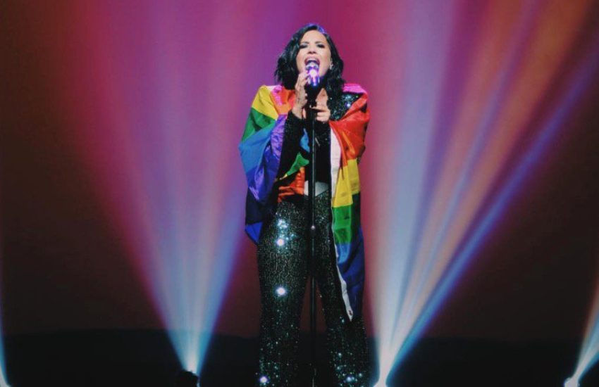 Demi lovato sings into a microphone stand with a rainbow flag draped over her shoulders