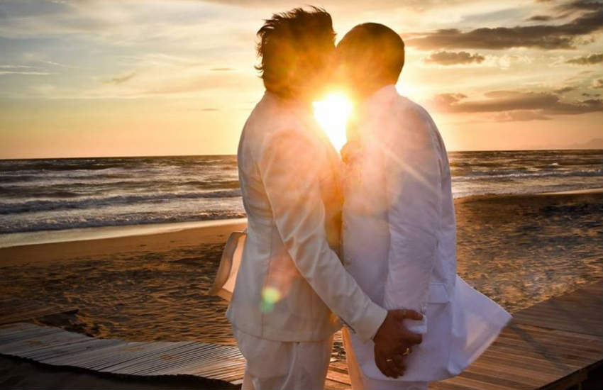 A gay couple in whit tuxedos kissing on the beach