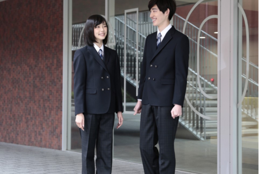 Two high school students standing next to each other in identical uniforms, they appear to be male and female