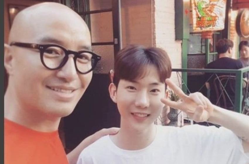 two men posing for a selfie, one is bald with glasses the other is wearing a white t-shirt and doing a peace sign
