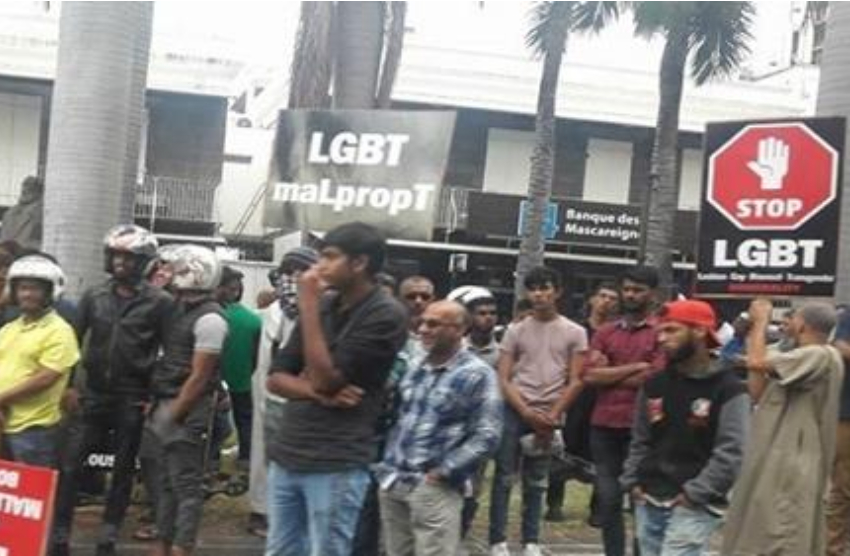a group of men standing in a street some are holding placards saying stop lgbt