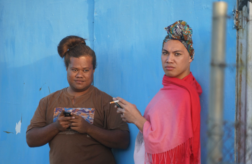 two people standing against a blue wall looking at the camera with a serious look on their faces