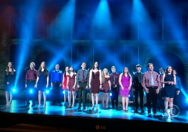 a groups of teenagers stand on a stage under soft blue lighting and are singing