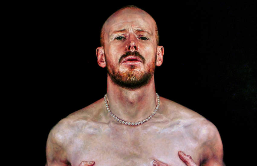 A portrait of a man squeezing his pecs while wearing a pearl necklace