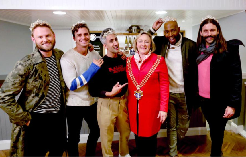 the five queer eye stars stand surrounding mayor rowena who's wearing her mayoral chain, the five men have tiaras on