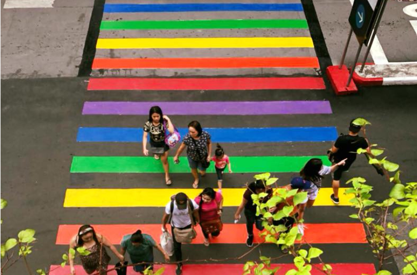 overhead photo of a rainbow crossing with people crossing