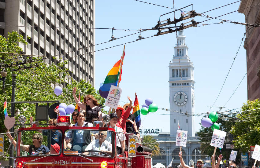 Floats at Pride Parade with the clock tower in the background