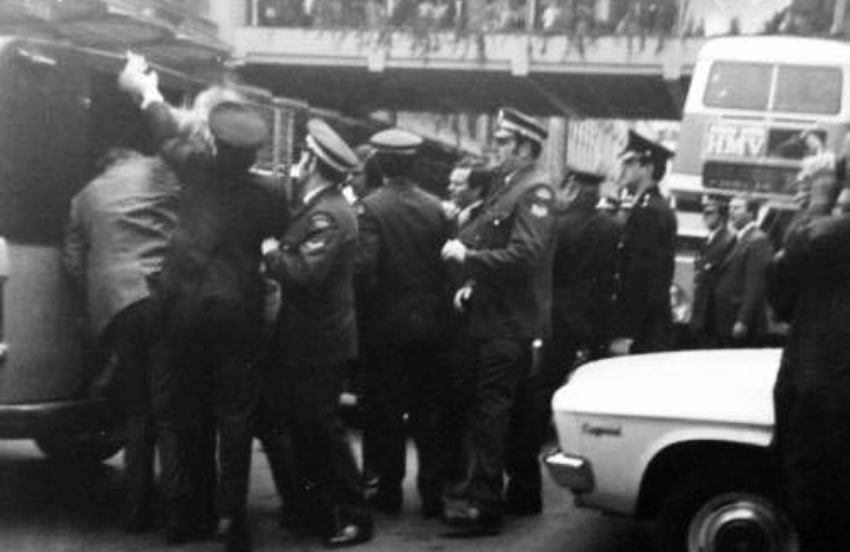 Black and white photo of a big group of police forcing people into police vans