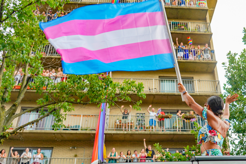 A person standing out the sun roof of a jeep holding a trans flag, waving to people in an apartment building