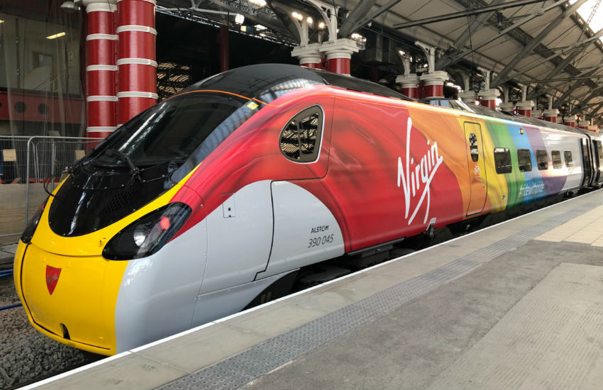 A Virgin Train decorated in rainbow colors for Pride season in the UK