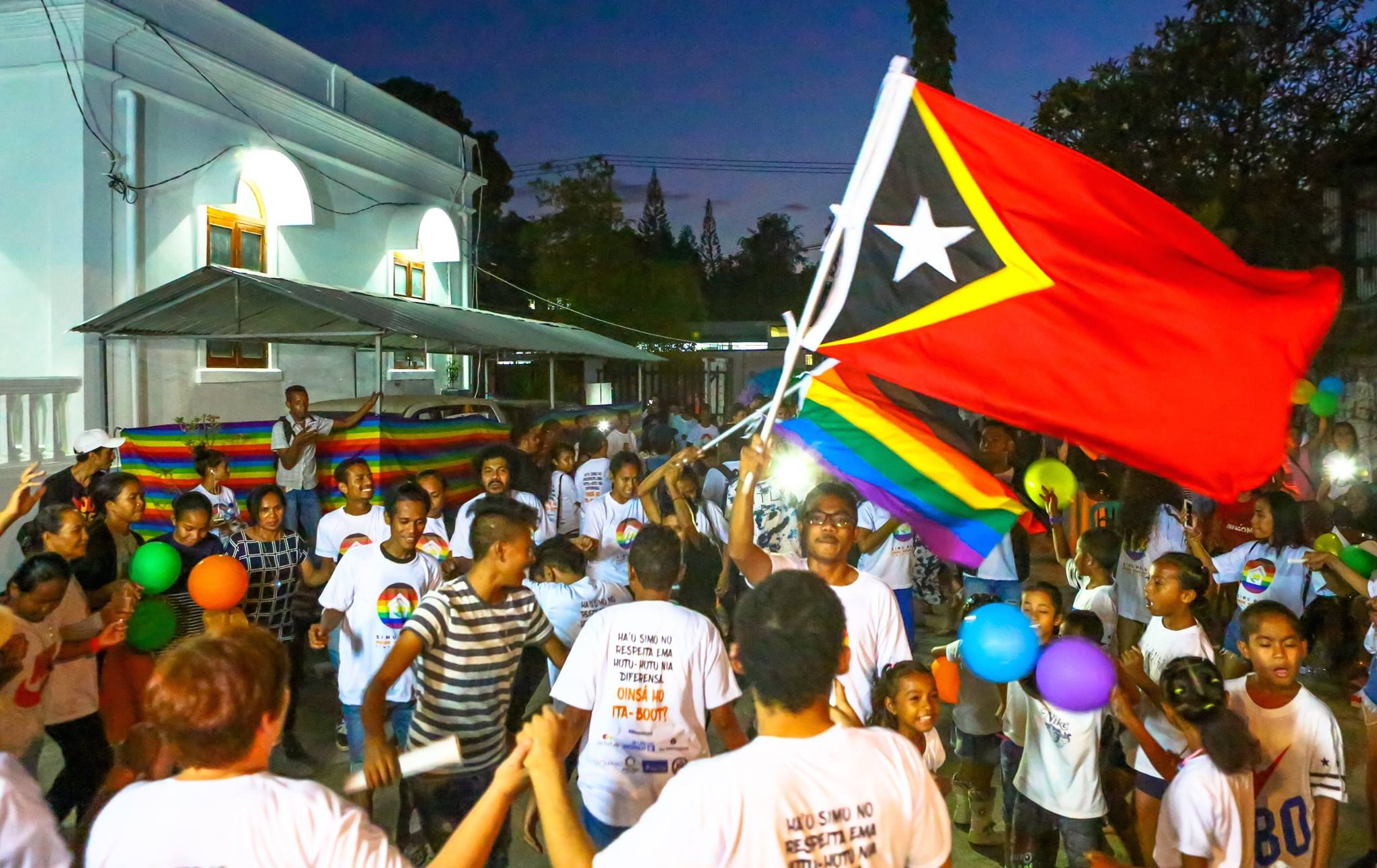 people standing outside a building at night dancing and celebrating. one person is waving a big east timor flag and the other is holding a rainbow flag