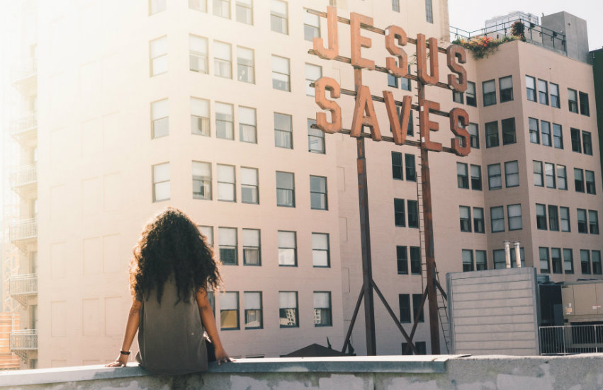 A young woman sitting in front of a sign that says Jesus Saves