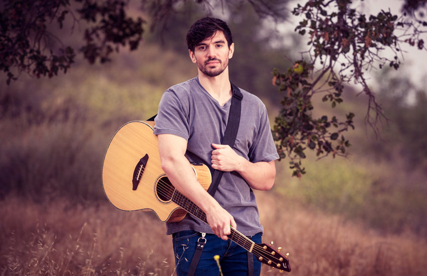 Steve Grand in field with guitar