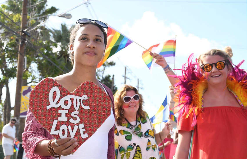 Marchers at Barbados' first pride. One of them is holding a 'love is love' heart-shaped sign