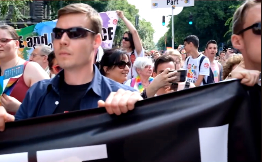 A close up of two men holding a black banner with dark glasses in the middle of a crowd they look very stern