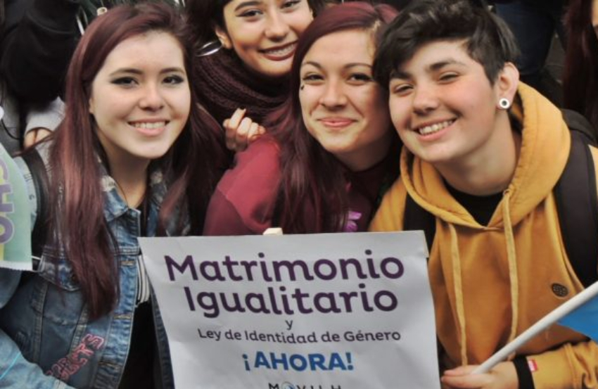 a group of young people huddled together smiling and holding a sign in spanish that reads, 'marriage equality, now'
