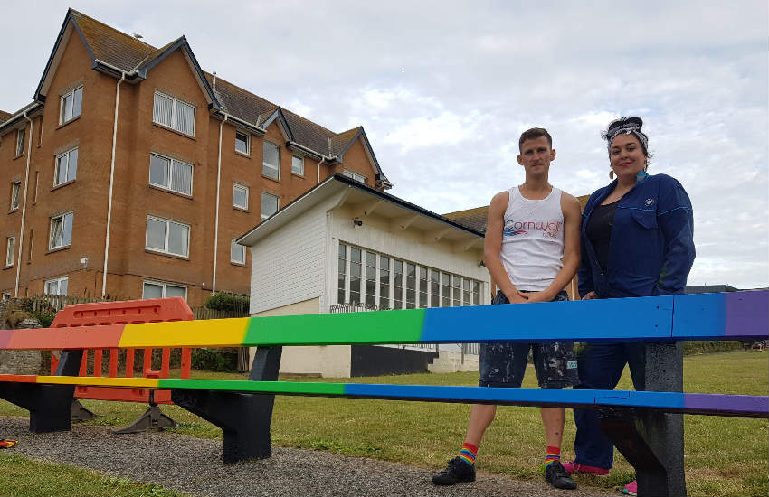 Two voluntarees standing beside the rainbow bench.