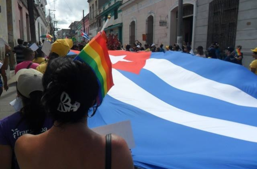 Photo behind a woman who has a rainbow flag sticking out of her ponytail and is standing next to a giant cuban flag at a public rally in Cuba