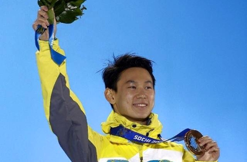 Denis Ten stands on the winner's dais holding up one arm his other hand is holding up his bronze medal