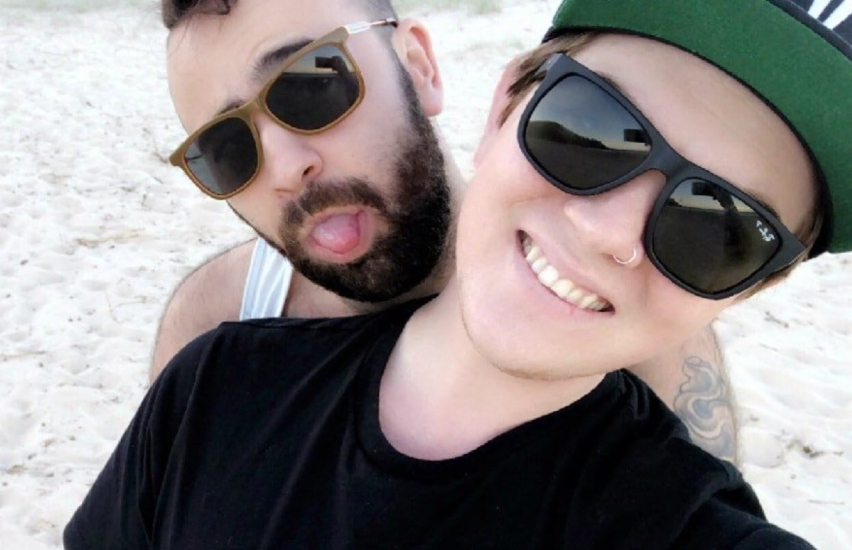 two men pose for a selfie on the beach one man standing behind the other with his arm's around him he has sunglasses, a beard and is poking his tongue out. The man at the front has dark sunglasses on and is wearing a baseball cap