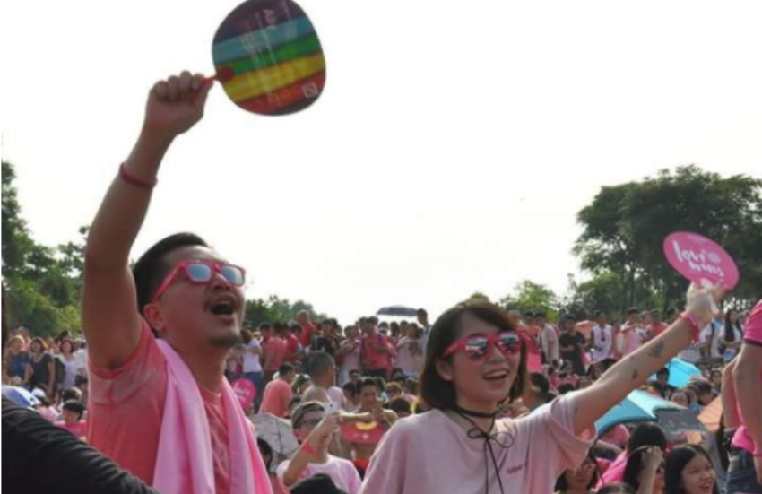 two people in pink t-shirts standing in a crowd waving colourful fans and smiling and singing