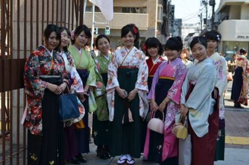 a group of girls in traditional japanese costume smiling at the camera