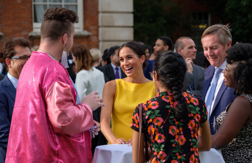 A group of people standing around a tall table at a garden party. Meghan Markle is in a yellow dress smiling at jacob thomas who is wearing a bright pink jacket