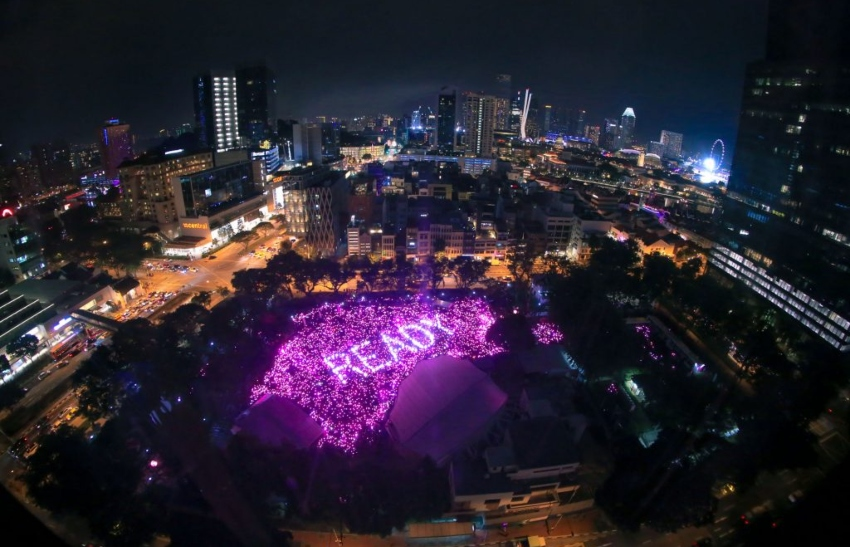 an aerial shot at night of a sea of people holding up pink lights, among the lights lighter pink lights spell the word ready