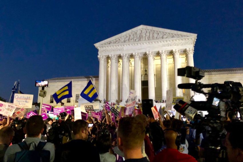 A shot behind a group of protesters standing outside the supreme court building at night