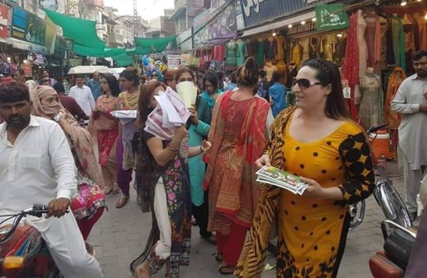 trans women handing out leaflets in a colourful pakistani market street