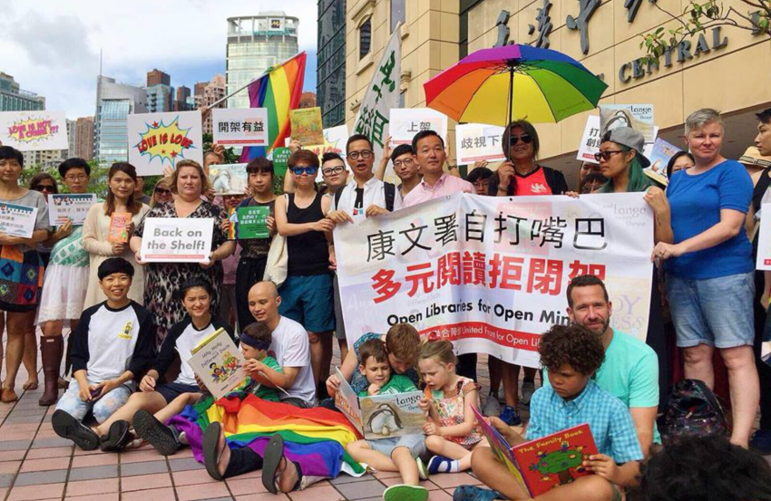 a group of people holding banners and signs in chinese and english. some people are holding rainbow flags and umbrellas. some people are sitting cross legged on the ground reading to children