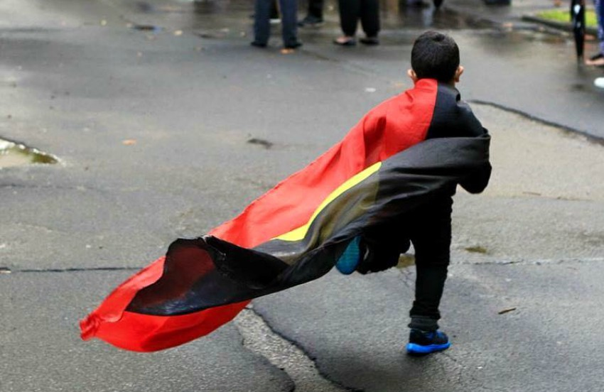 a small child running down the street, the aboriginal flag is tied around his shoulders and is flying behind him as he runs