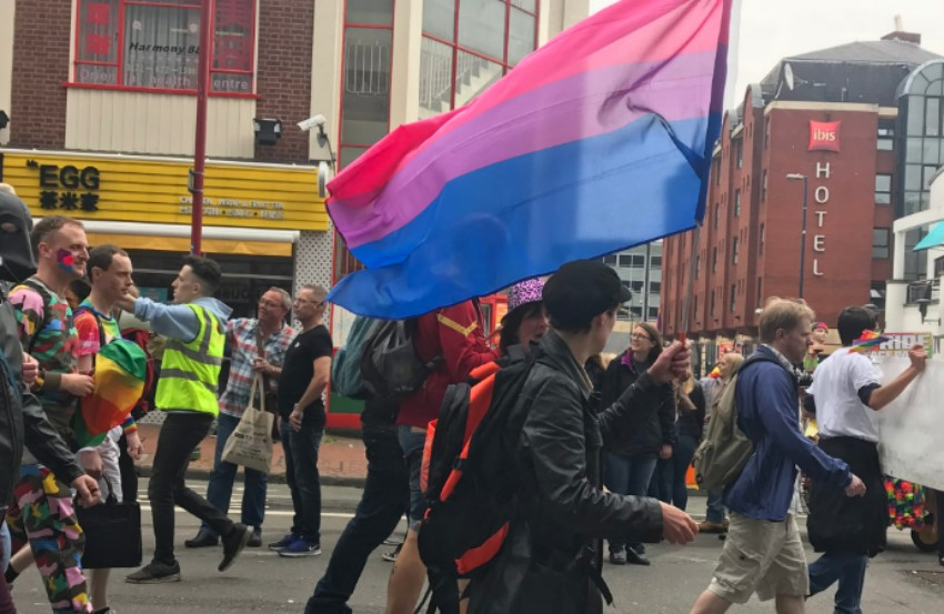 a person walking in a parade holding a bisexual flag