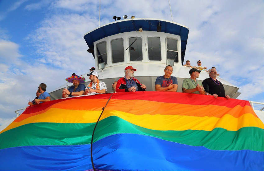 People on a boat unfurling the rainbow flag.