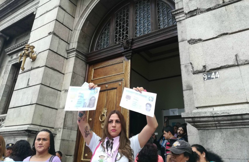 a woman standing outside an official looking building holding two pieces of paper in the air