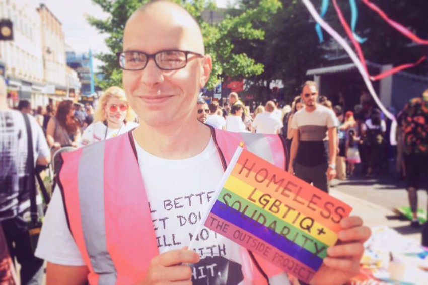 a man at a pride parade wearing a pink hi vis vest holding a small rainbow flag that has 'homeless lgbtiq+ solidarity'