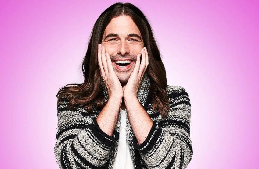 jonathan van ness stands with his hands on his cheeks smiling widely at the camera, he's wearing a brown knit cardigan over a white t-shirt