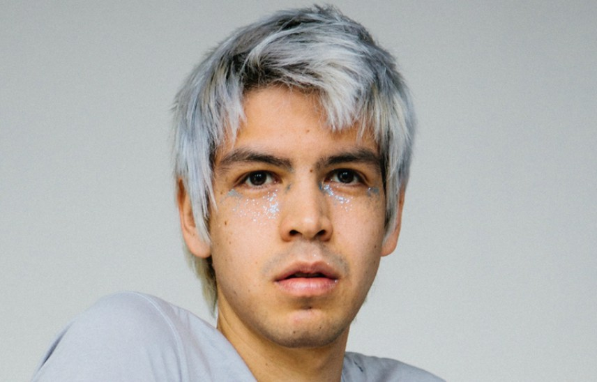 head shot of julio torres, he as silver grey short hair and grey glitterunder his eyes