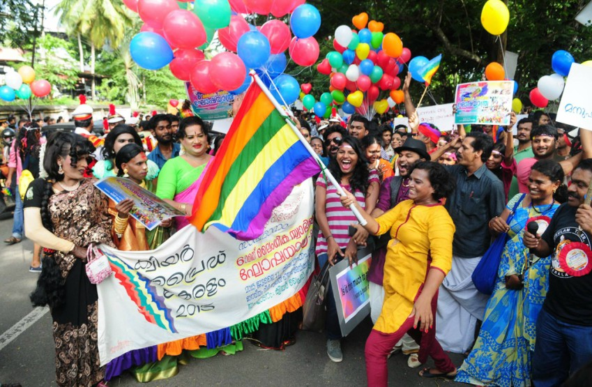 a group of people standing on a street at a pride parade holding banners and rainbow flags, colourful balloons are above them. everyone is smiling