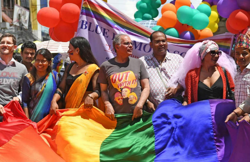 People holding a rainbow flag during Nepal Pride