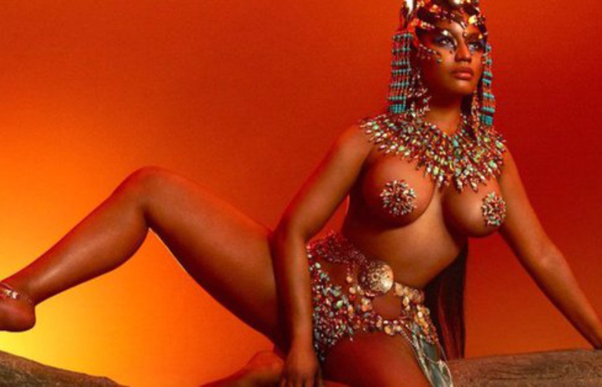 nicki minaj sits across a tree branch in revealing ancient egyptian costumes