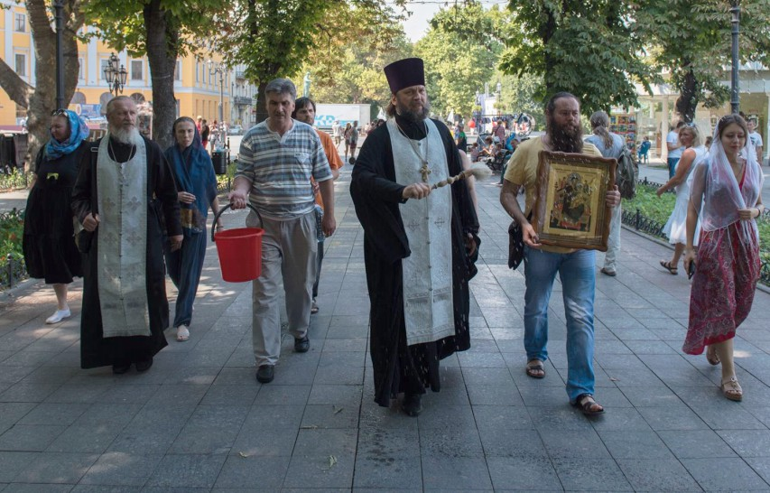 A group of people walk behind a priest in a street