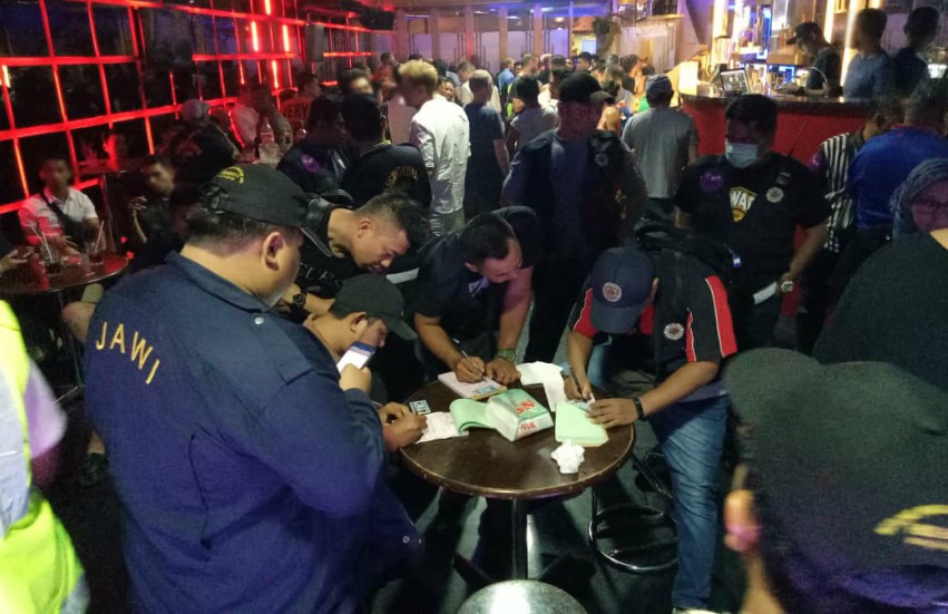 a group of authorities stand around a table in a crowded bar filling out forms while the people at the bar stand around