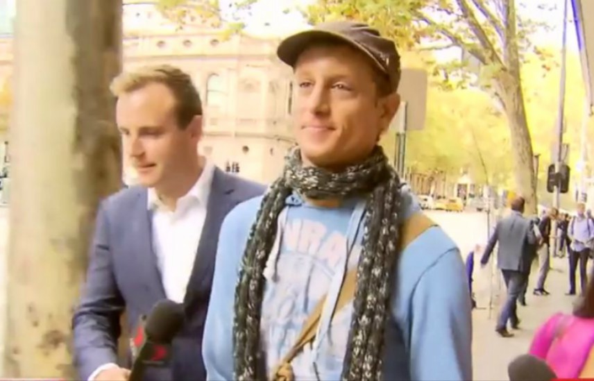 a man in a hat and scarf walks down the street as journalists with microphone chase him