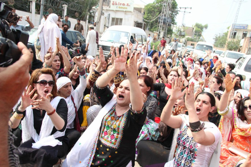 a group of women protesting they have their arms in the air and are shouting